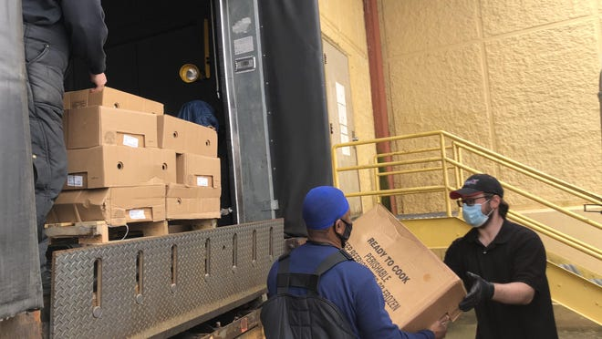 Workers load food items that were recently donated to Meals on Wheels of Texoma by Ruiz Foods.