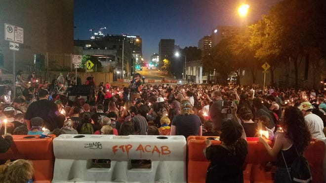 More than 100 people joined in a candle light vigil ceremony on Friday night in front of the Austin Police Department headquarters.