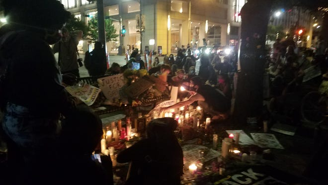 Protesters in Austin on Monday held a moment of silence in front of a memorial dedicated to Garrett Foster at the corner of Fourth Street and Congress Avenue. Foster was shot and killed on Saturday while participating in a Black Lives Matter protest.