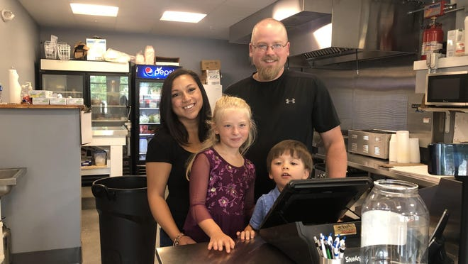 Doug and Alicia Colwell with children Cali and Gavin in the newly reopened Doug's Hoagies shop, located in the new Fourth Street Depot building.