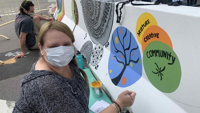 In July and August, 50 artists from the Putnam area and other residents flocked to the town's  downtown to paint a mural on the barriers.