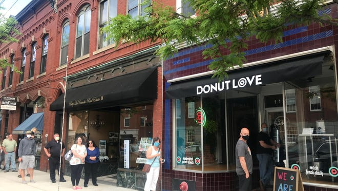 """Exeter residents line up to try the offerings at Donut Love's new downtown location at 127 Water St. Owner Mike Oliveira called the buzz surrounding the opening of his award-winning donut shop """"phenomenal."""""""