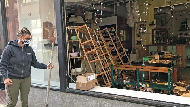 Karen Beebe cleans up broken glass outside Modern Love on Westminster Street.