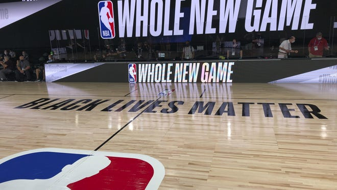 "A basketball court at the ESPN Wide World of Sports complex in Kissimmee, Fla., displays the NBA's marketing motto, ""Whole New Game,"" for the restart of the season at Walt Disney World."