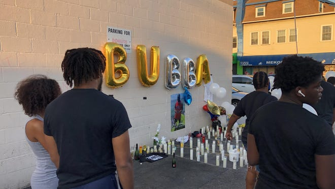 "Mourners lit candles and arranged them beneath a string of balloons that read ""Bubba"" in honor of a man killed in a Dunkin' parking lot on Broad Street early Saturday."