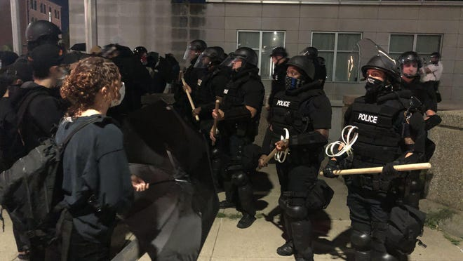 Protesters and police in riot gear outside the Providence Public Safety Complex Sunday night.