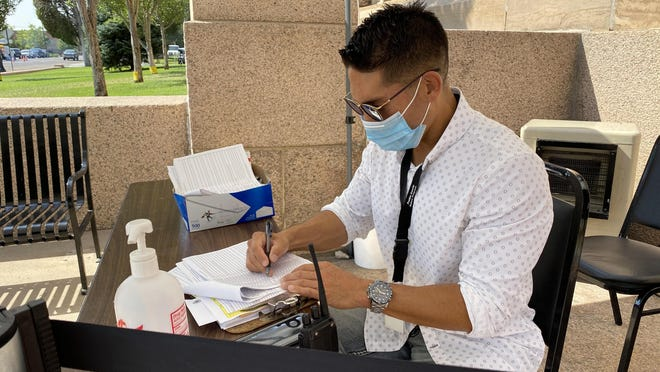 Ralph Valdez checks in a Pueblo County citizen who had an appointment with the department of motor vehicle office Thursday.