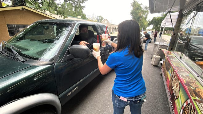 Devin Vaughn, the Colorado State Fair's grounds entertainment and rental director, hands drinks to Greg Chamberlain during Friday's opening of Drive Thru Fair Food.