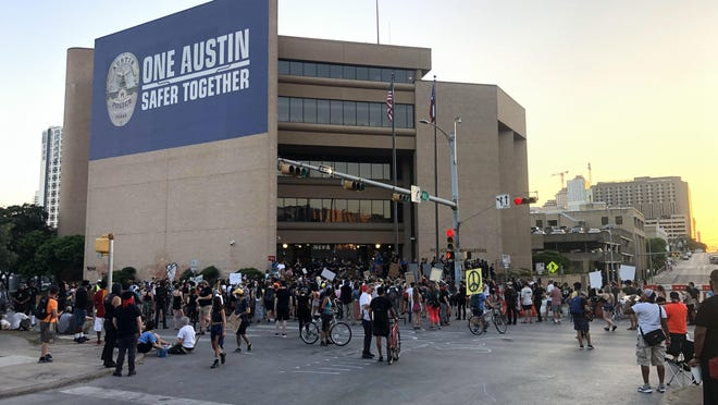 The crowd of protesters outside Austin police headquarters remained calm Sunday evening as many people and police officers engaged in individual conversations throughout the evening.