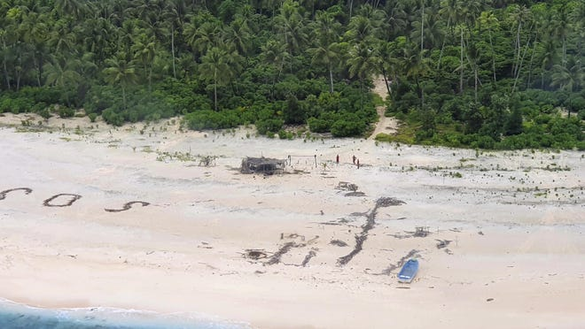 "In this photo provided by the Australian Defence Force, three men stand the beach on Pikelot Island in the Federated States of Micronesia Sunday, Aug. 2, 2020, where they are found safe and healthy after missing for three days. The men were missing in the Micronesia archipelago east of the Philippines for nearly three days when their ""SOS"" sign was spotted by searchers on Australian and U.S. aircraft, the Australian defense department said."
