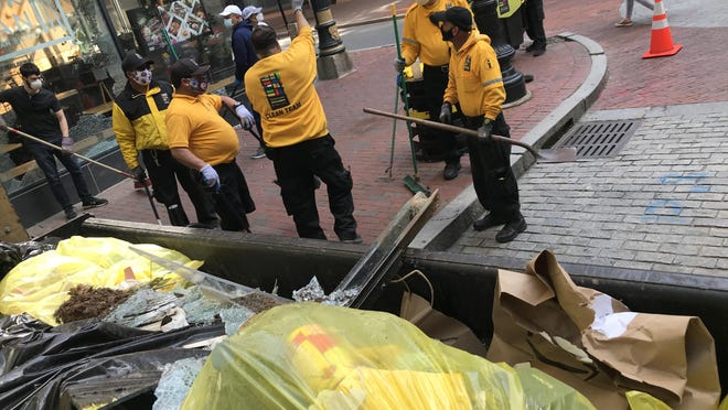 Workers clean debris from Westminster Street after a riot in downtown Providence early Tuesday.