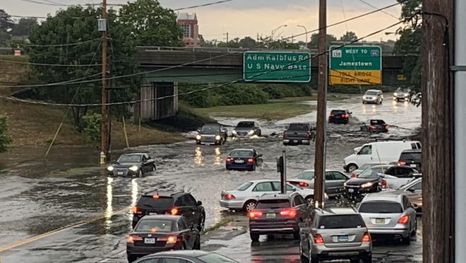 Some cars drive through the flooded roadway on JT Connell Highway in Newport, while other avoid it after a heavy downpour Tuesday afternoon.