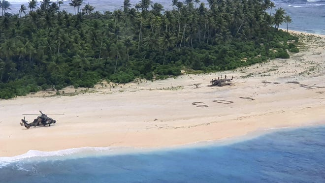 In this photo provided by the Australian Defence force an Australian Army helicopter lands on Pikelot Island in the Federated States of Micronesia where three men were found, Sunday, Aug. 2, 2020, safe and healthy after missing for three days. The men were missing in the Micronesia archipelago east of the Philippines for nearly three days when their 'SOS' sign was spotted by searchers on Australian and U.S. aircraft, the Australian defense department said.