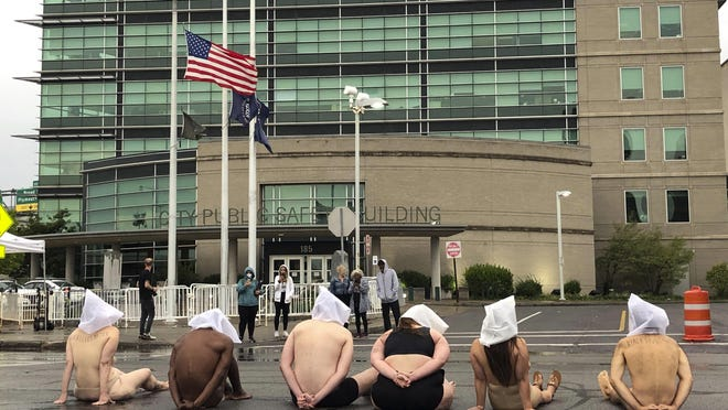 Naked protesters at Rochester's Public Safety Building Monday.
