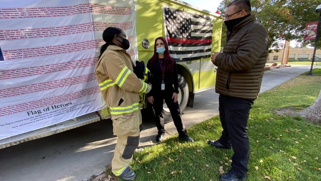Kristina Harris, who helps with fire training at Pueblo Community College, left, and Pueblo Law Enforcement Academy cadets Ruben Trujillo and Dezarae Nish honored first responders and victims of the 9/11 attacks during a tribute at PCC Friday.