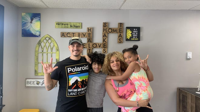Omar Sonera and Jasmin Cox pose with Cox's children, Uriah, 12, and Abigail, 7, inside their smoothie and juice bar, One Love Nutrition in Mount Pocono.