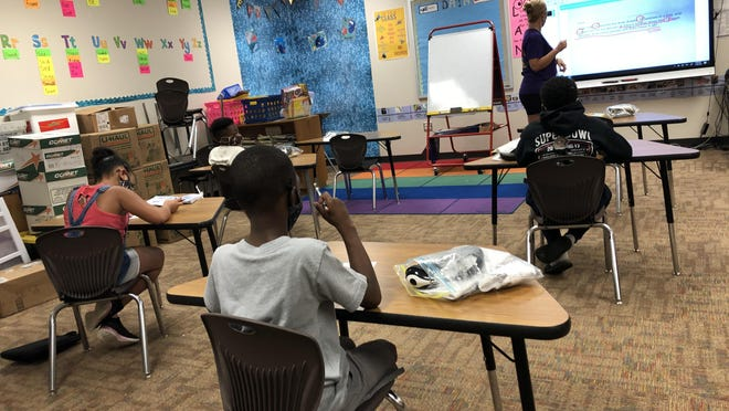 Students at Ervin Elementary School sit at a distance and wear masks during school this summer.