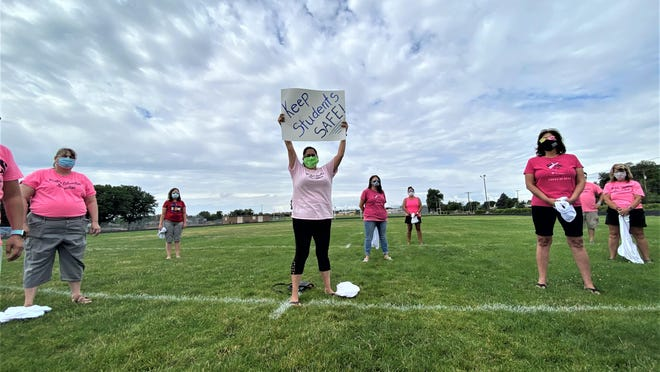 Pueblo Education Association member Claudia Garcia holds aloft a sign after removing a white shirt to reveal the familiar PEA pink.