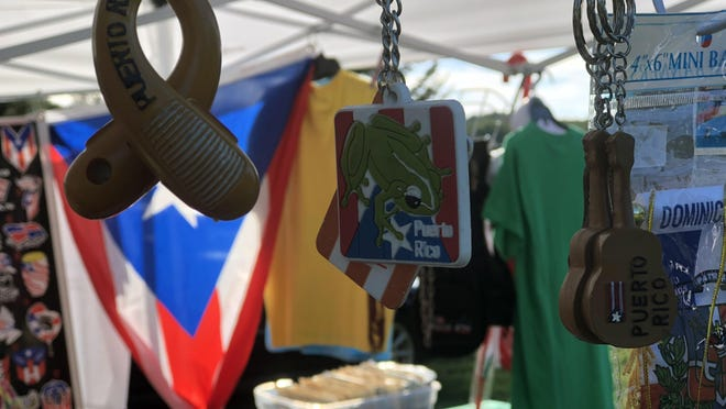 FILE- Puerto Rican and other Latin heritage souvenirs hang from supports in Norma Galarza's booth at the 2018 Latin Fest in Coolbaugh.