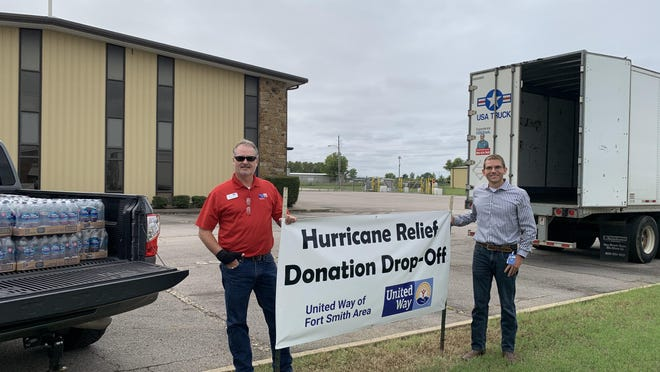 Eddie Lee Herndon, president and CEO of United Way of Fort Smith Area, and Edwin Anglin, assistant general counsel of USA Truck stand at a hurricane relief drop-off location in Van Buren.