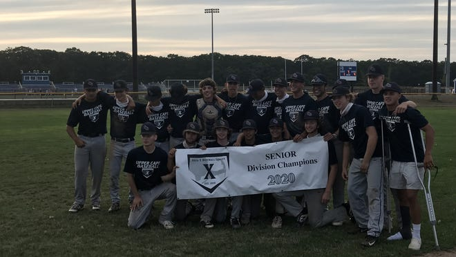 The Upper Cape baseball team poses for a picture with their Area X Baseball championship banner, after beating Wareham 4-1 in the final game at Fenton Field at Sandwich High School in East Sandwich Friday.