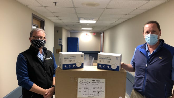 At one of the mask deliveries are Edward F. Manzi Jr., left, chairman and CEO of Fidelity Bank, and Steve Roach, interim president of UMass Memorial HealthAlliance-Clinton Hospital.