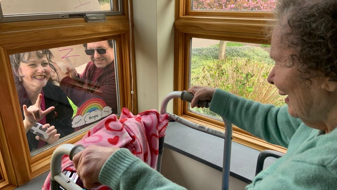 Rebecca Cordner, and her brother Don, during a window visit with their mom, Kathie, on April 19, 2020.  Rebecca is signing.
