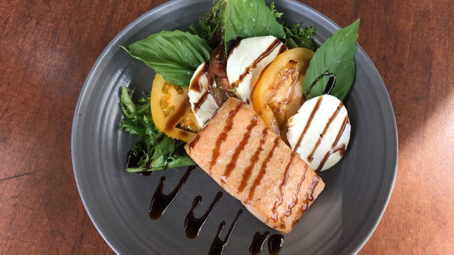 Salmon filet atop a caprese salad with fresh mozzarella, heirloom tomatoes and greens, is a simple but elegant meal at The Brewster Fish House.