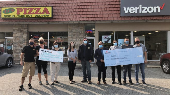 Employees of TJ's Pizzeria Cafe and Verizon premium retailer R-Wireless display checks showing $1,600 raised for the Sussex County C.L.E.A.R. program outside their Franklin stores Tuesday, Sept. 15. Pictured from left are: Steven Freaney, TJ's co-owner; Tammy McTeague, TJ's manager; Becky Carlson, C.L.E.A.R. co-founder and Center for Prevention and Counseling executive director; Katie Calvacca, Center for Prevention and Counseling recovery coach; Mike Richards, C.L.E.A.R. co-founder and former Newton Police Chief; Amit Singh, R-Wireless director of sales; Elvin Rodriguez, R-Wireless assistant manager; Andrew Szanyi, R-Wireless sales associate; and Ryan Bradley, R-Wireless general manager.