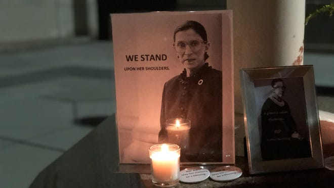 Photos of U.S. Supreme Court Justice Ruth Bader Ginsburg are displayed during a candlelight vigil Saturday night outside the Rhode Island Supreme Court.