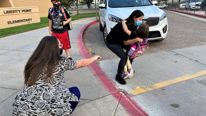 At right, Stephanie Thompson gives her daughter, Aurora, a hug, as Randi Moore, occupational therapist assistant, awaits the arrival of the kindergartener outside Liberty Point Elementary School on Monday. Looking on is Thompson's son Tyler.