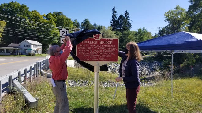 "Jim Ninos, left, and Debra Jakobi, right, unveil a ""Legends and Lore"" marker that details the origins of the Baker's Bridge hamlet in Alfred Station on Saturday."