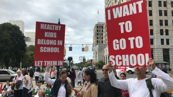 Protestors last September hold signs in opposition to a law that bans religious exemptions from vaccinations during a rally outside the state Education Building in Albany.
