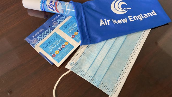 """A kit of COVID safety related products is given to passengers of Air New England, a charter airline service out of the Portsmouth International Airport in Pease that saw a """"really big pick up"""" of business during the summer months."""