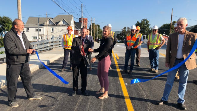 Joe Liberto, a Hornell Department of Works commissioner, and Jeff Brown, 3rd Ward alderman, hold the ribbon as Mayor John Buckley and business owner Brandi Greenthal give the ribbon a snip to mark the re-opening of the Seneca Street bridge Wednesday morning.