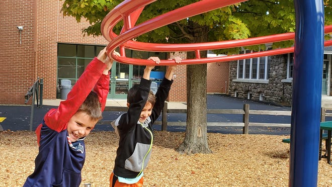 Ryder Raizes, 6, and his friend Aiden Cresta, 6, check out one of the new pieces of equipment on the playground at Greenland Central School.