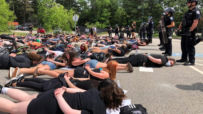 Hundreds marched to the Sanford Police Department headquarters on Saturday, June 6, 2020, where about two dozen officers stood silently with shields and weapons. The demonstrators, who were organized by Project CommUnity, lay on the ground in a manner reminiscent of the way George Floyd died in Minneapolis.