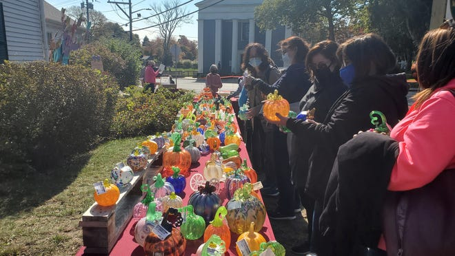 Attendees of the ninth annual PumpkinFest line up to look at the assorted glass pumpkins for sale Sunday. The Sandwich Glass Museum usually hosts the event under a tent, but glassware was displayed in the open air this year due to the COVID-19 pandemic.