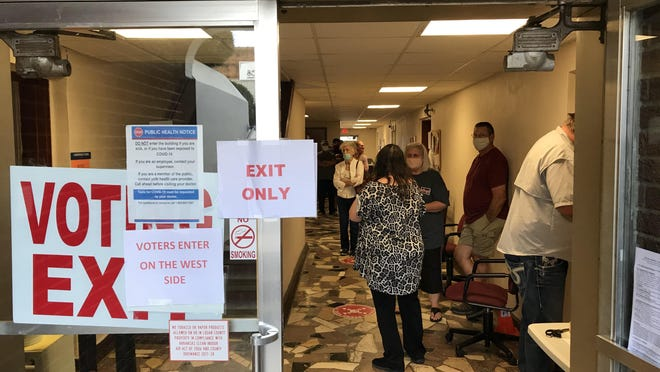 Early voters stand socially distanced at the Logan County Courthouse in Paris on Wednesday, Oct. 21, 2020. There has been an increase in both early voting and absentee ballots this election cycle, according to the county clerk.