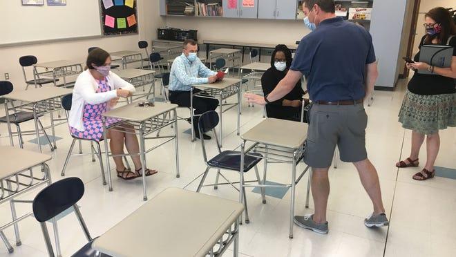 Plymouth South Middle School Principal Joe Murphy shows members of the School Committee what 3 feet of spacing looks like.