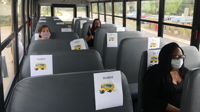 Plymouth School Committee members Michelle Badger, Kim Savery and Vedna Heywood get a feel for social distancing requirements on local school buses. Only one student will be allowed on each bench seat, cutting the number of students per bus from 71 to 23.
