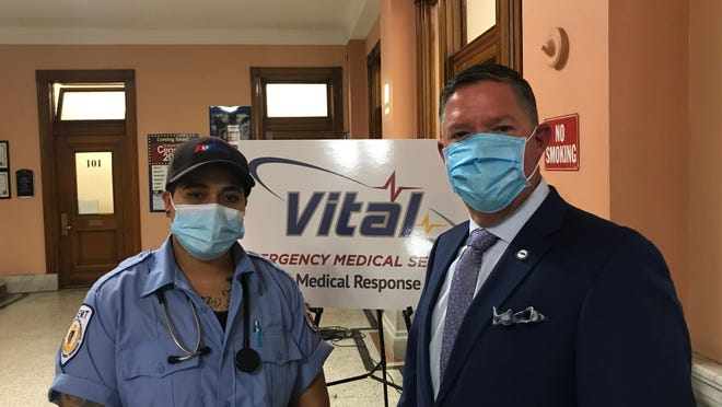 Tatiana Adorno, left, a graduate of the Springfield Earn While You Learn program for EMTs, stands at Worcester City Hall on Wednesday with Patrick Pickering, northeast director of American Medical Response. The company will pay 25 local residents' training and test fees to become EMTs and help fill an industry shortage.
