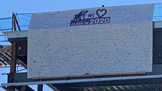 The banner signed by the Belmont High School graduating seniors is temporarily hanging on the new Belmont Middle and High School building under construction.