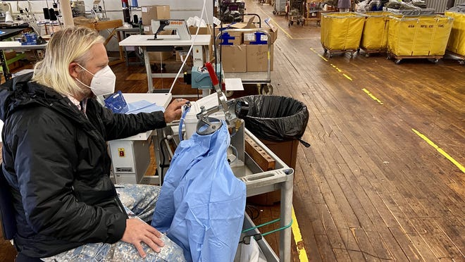Charlie Merrow, CEO of Merrow Manufacturing, puts a competitor's isolation gown through a water test in his Bedford Street building. The medical garment flunked the test.