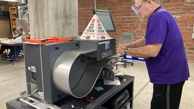Sebastian County Elections employee William Craig loads the first load of 50 ballots into the new DS450 machine to be processed.
