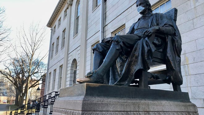 The John Harvard statue at Harvard University, a popular tourist attraction at the campus in Cambridge, sits adorned with a medical mask as students prepared to leave campus, on  March 14.