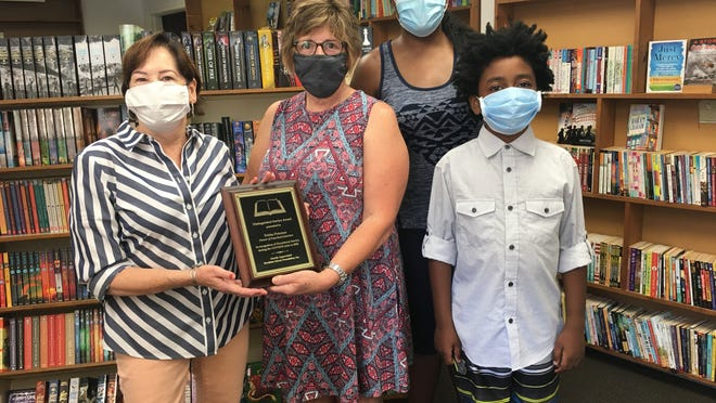 The Brockton Library Foundation presented Paperback Junction owner Trish Peterson with a plaque thanking her for her help providing 1,700 books to Brockton residents. From left are Peterson, foundation vice president Brenda Rodrigues, Foundation treasurer Nicole Green and her son, Tyler at the Easton shop on Aug. 5.