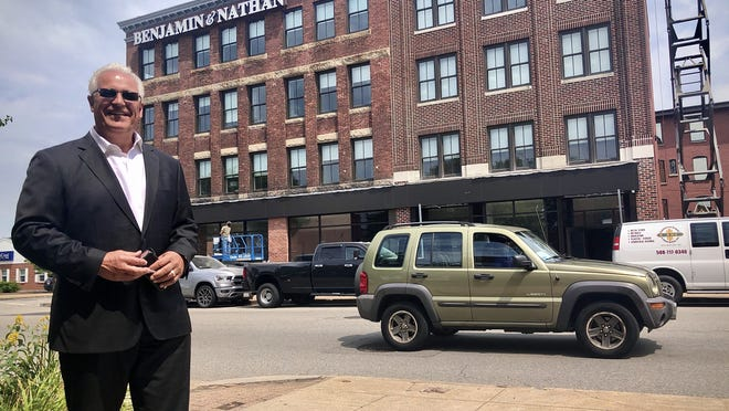 Real estate developer Tony Cordeiro stands across from the Pleasant Street building where he has created 20 new apartments.