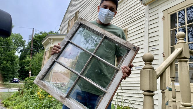 Sergio Quiroa holds a nearly three-century-old window at the Clara Sexton House.