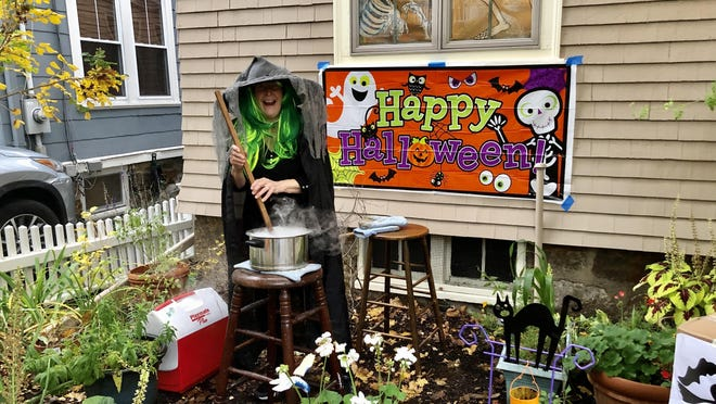 Orlene Hagedorn stirred a cauldron with dry ice in front of her house on Brook Street Oct. 31, 2019.
